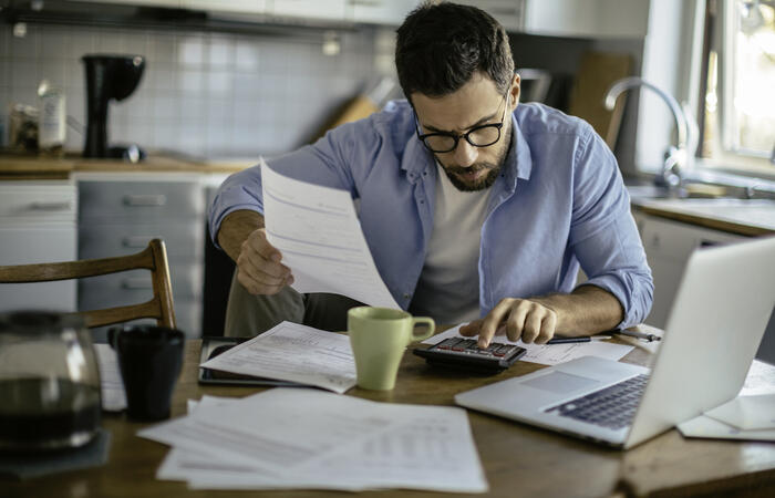 Man sorting out paper bills in front of computer